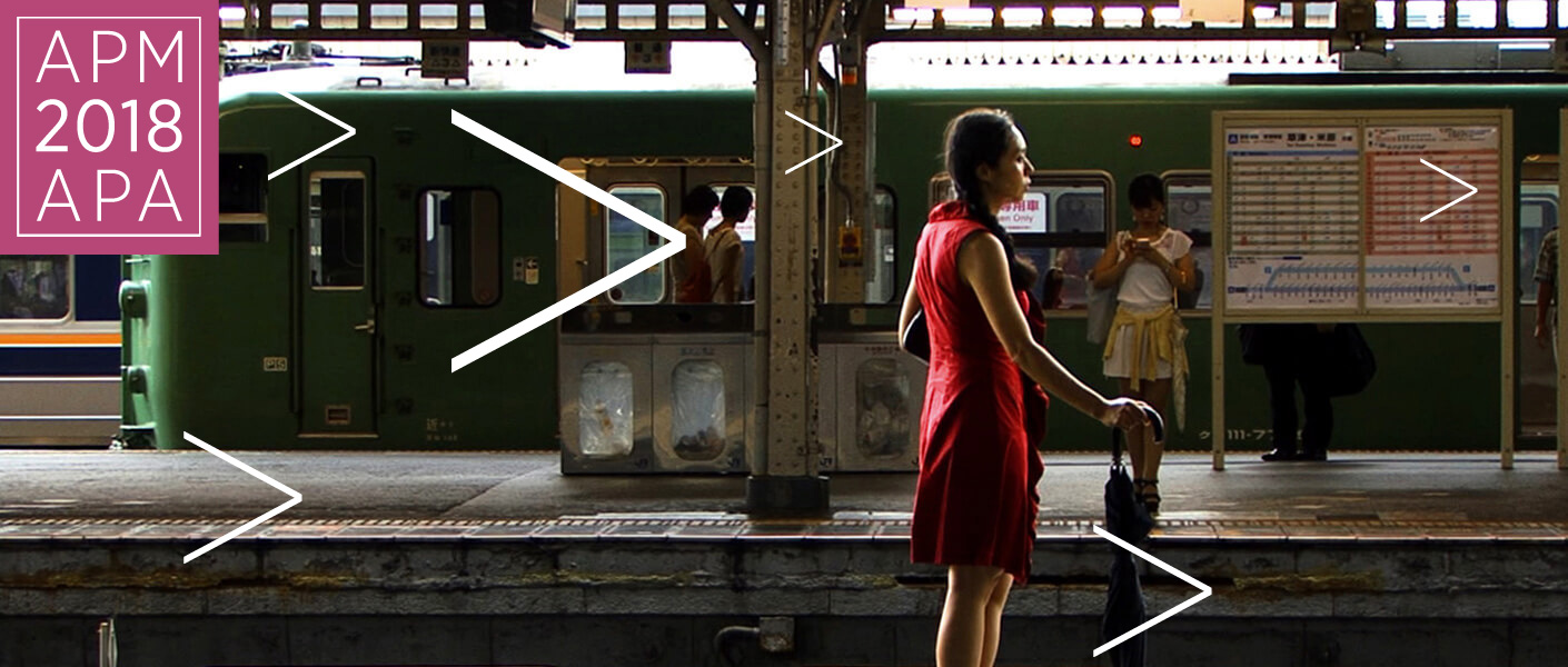 Woman in a red dress waiting for a train