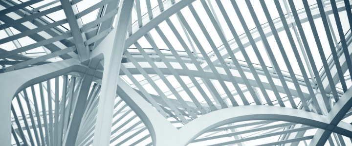 Ceiling view of a galleria covered with a canopy of intertwining steel arches.
