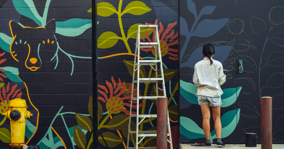 Young woman with black hair creating a mural in an urban setting.