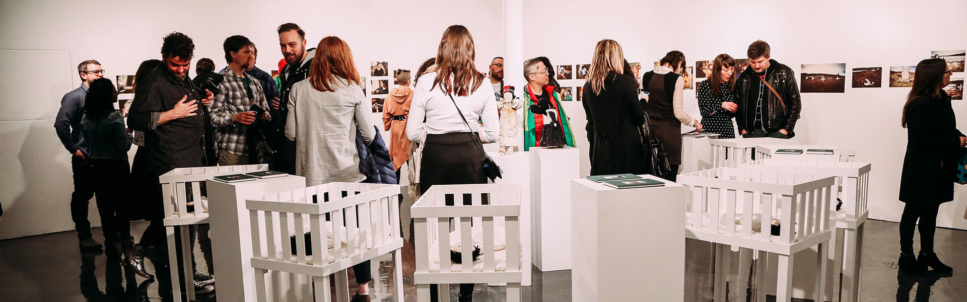 A small crowd of people viewing art on walls and in displays.