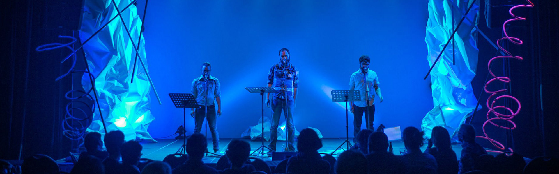 Three performing poets declaim their texts on a stage illumined by bright blue lights.