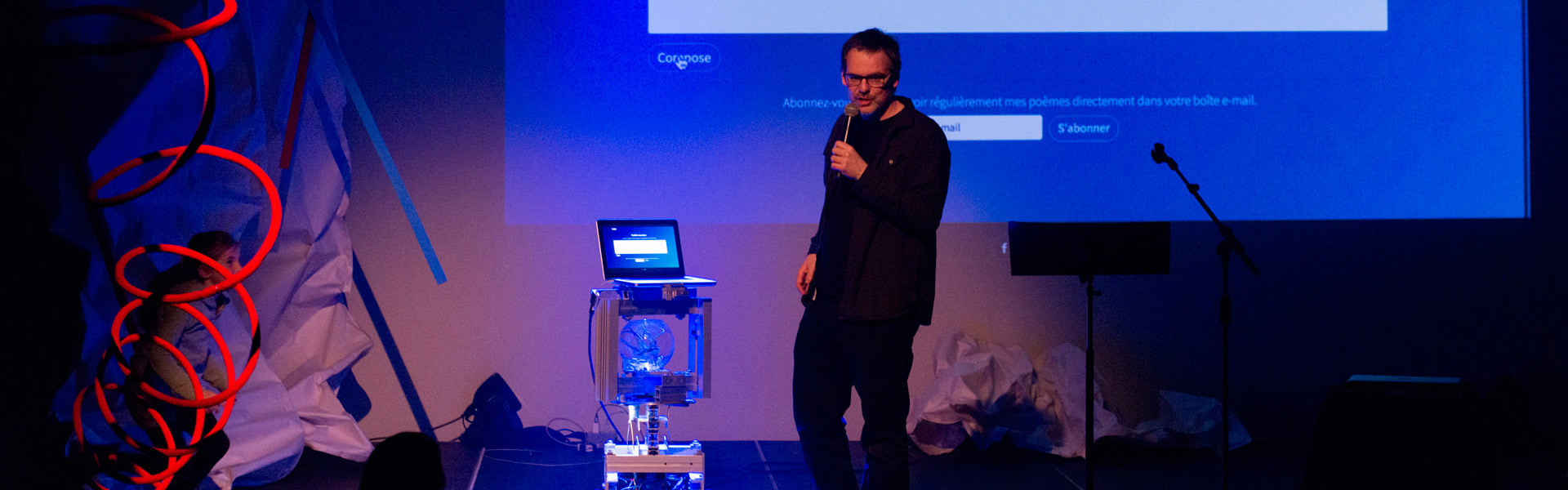 The conversational robot PaulBot is seen on stage under blue-tinted lighting, alongside its creator and in front of a screen displaying his poems in Chiac.