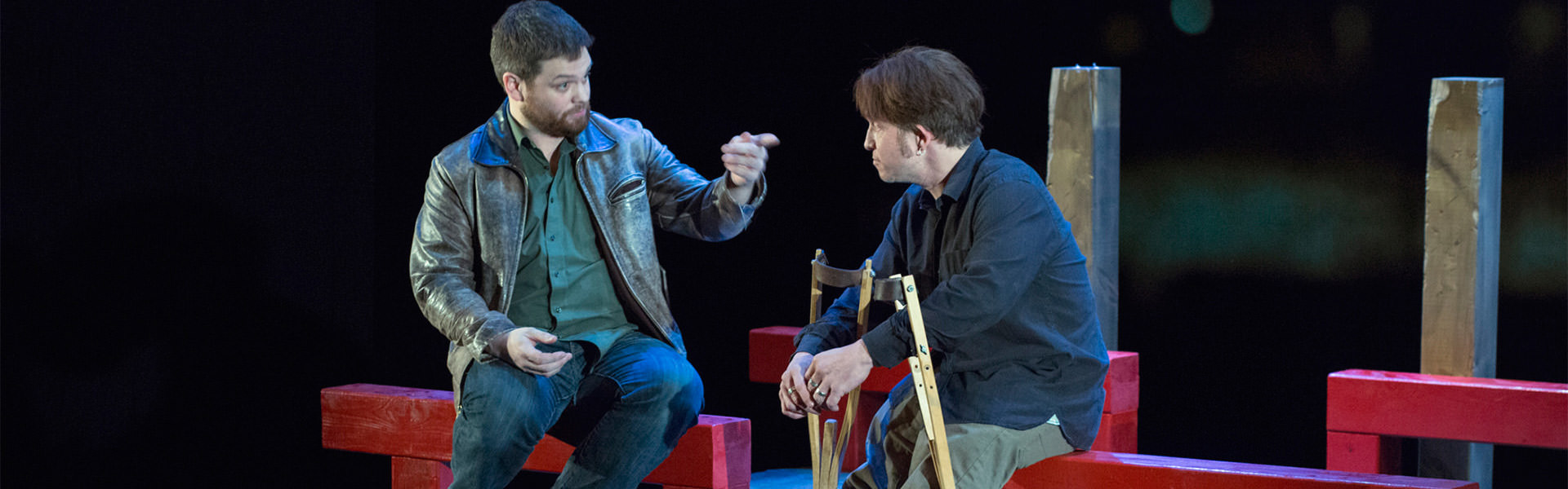 A scene from opening night of Crippled. Actors Pat Dempsey and Paul David Power seated and talking.