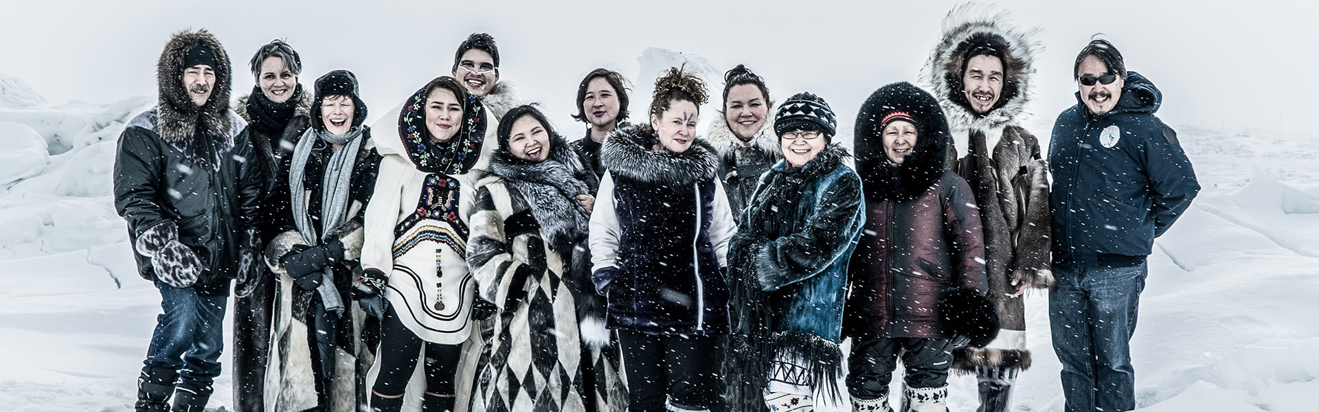 A dozen members of the Kiviuq Returns cast pose against a snowy backdrop.