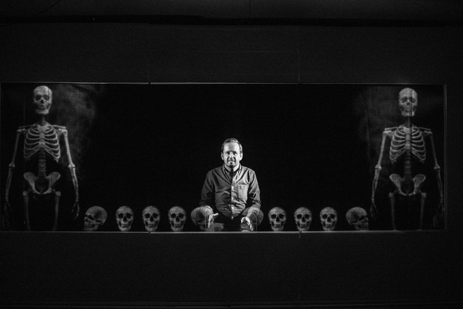 Actor Jay Whitehead is shown centre stage, surrounded by projections of human skulls and skeletons.