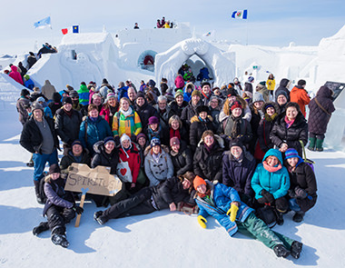 The Spiritus Chamber Choir joined by composer Carmen Braden and members of the string ensemble, pose for a group shot at the famous Snow Palace in Yellowknife, NWT.