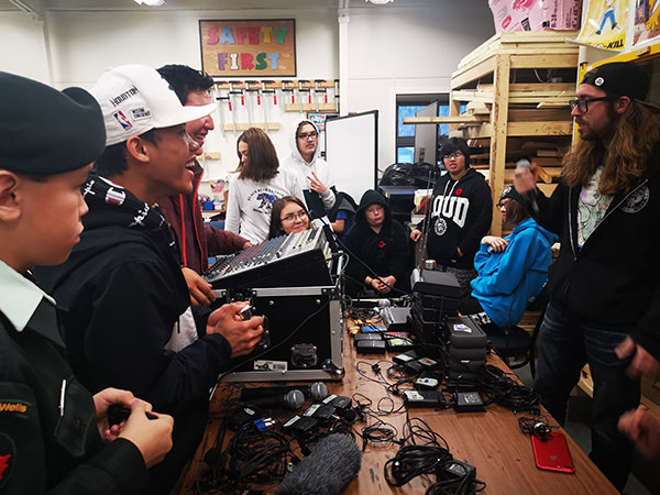 Indigenous youth surrounded by audio equipment on a table.