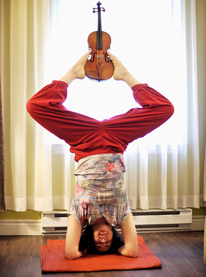 Maria Millar holds her violin with her feet as she does a handstand