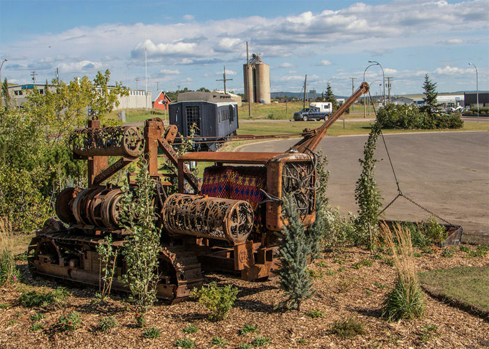 Rusted industrial machine repurposed as public art surrounded by shrubs, a train car and grain tower exist in the background