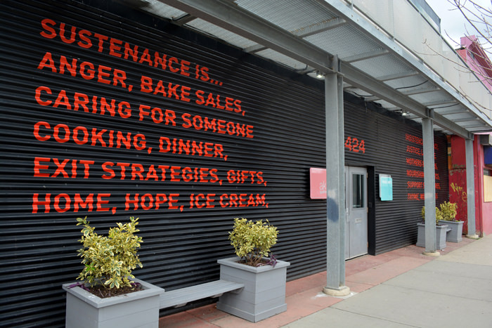 Large text on an exterior wall of AKA artist-run centre, defining sustenance in new ways
