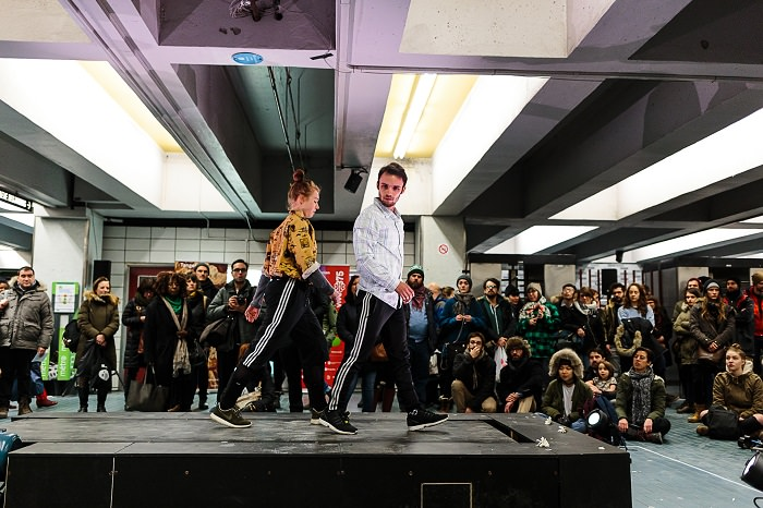 In the metro an oversized treadmill is a rolling stage for young contemporary dancers in sport pants and light shirts. Spectators gather around them.