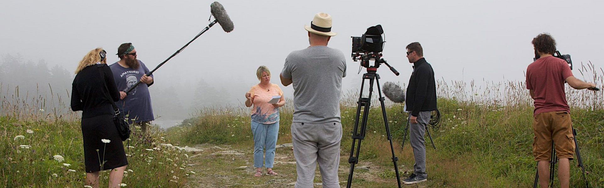 A film crew stands around a woman who is speaking; they are in a field of grass surrounded by fog.