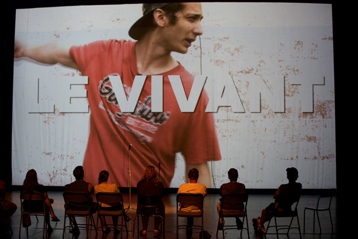 "A screen shows a young man and the text ""Le vivant"" overlaid. There are several people in chairs with their backs to our view on a stage, looking at the screen."