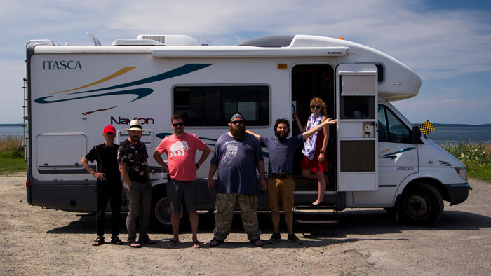 Six members of a team stand together in front of a caravan. It is a sunny day in a rural place, grass and a body of water exist in the background.