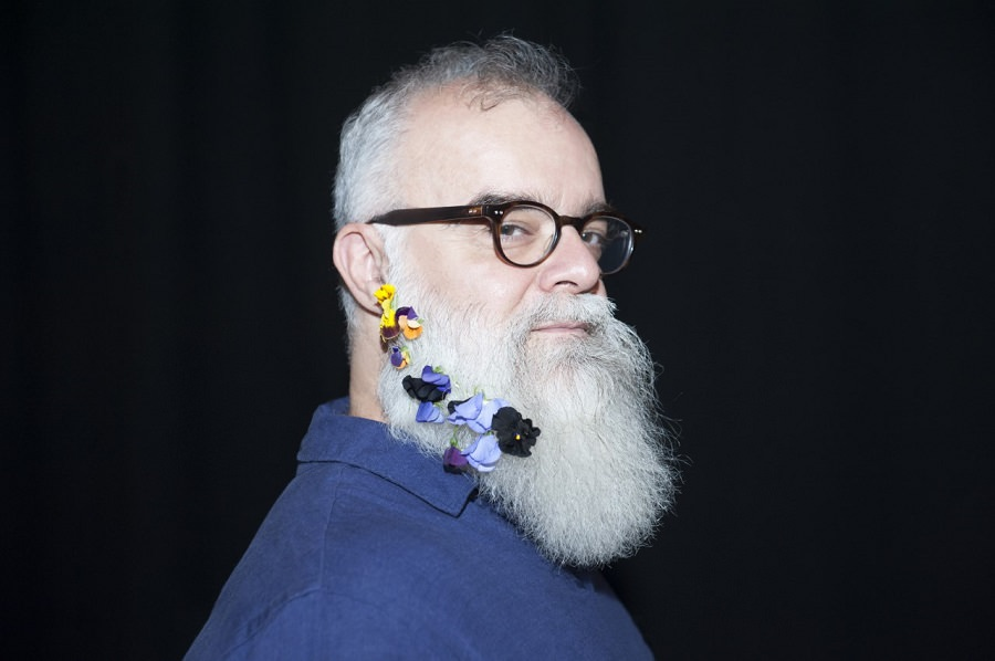 Rodney Sharman, composer, poses with flowers in his beard.