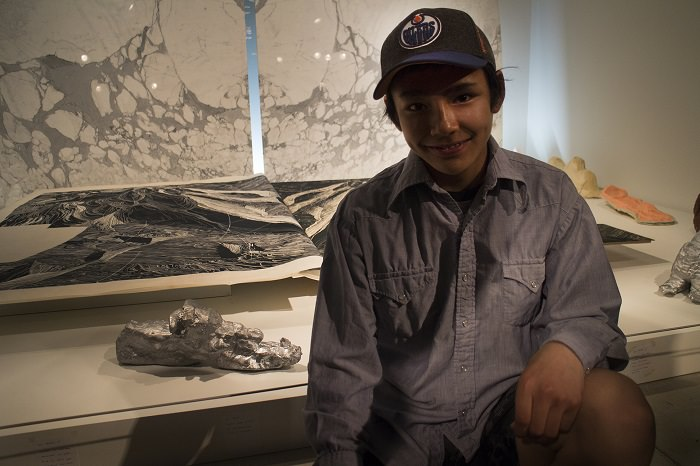 A young boy named Lachaolasie sits in front of artworks at the AGO, including his sculpture of a snowmobile