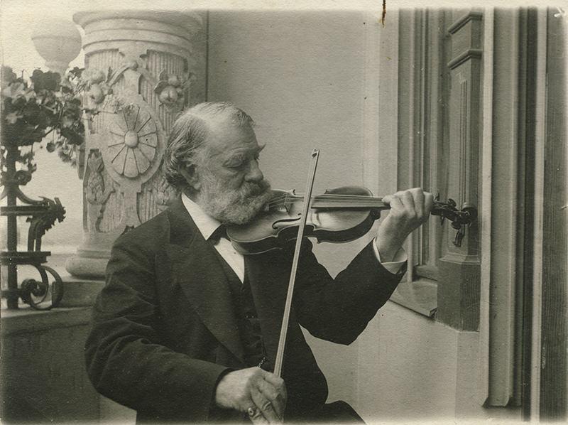 Black and white photo of Hungarian violinist Joseph Joachim plays a violin