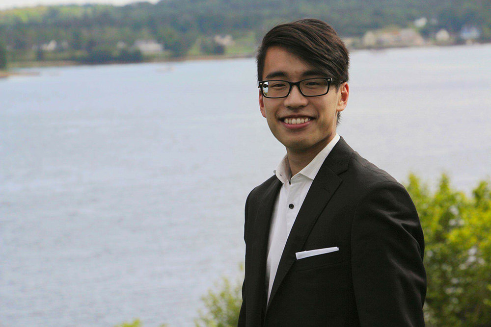 Jonathan Mak in formal wear, stands by lakefront.