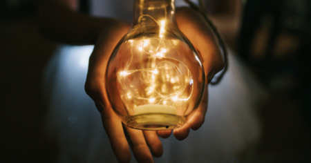A pair of hands holding a light bulb